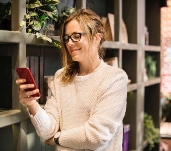 Frau lächelt auf ihr Handy