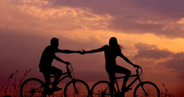 Paar hält Händchen auf dem Fahrrad